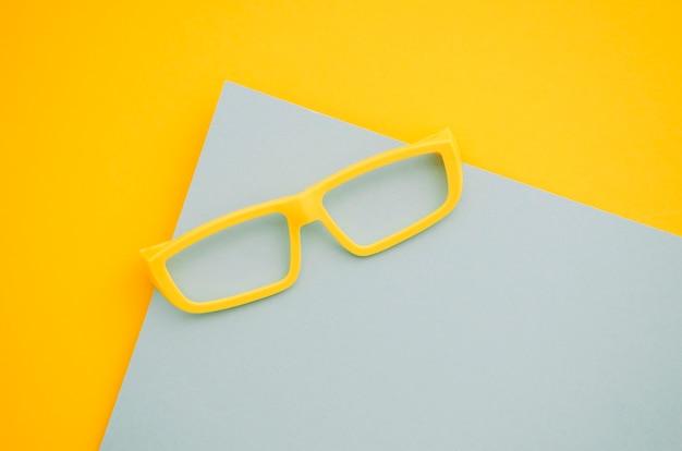 Gelbe kinderbrillen auf grauem und gelbem hintergrund Kostenlose Fotos