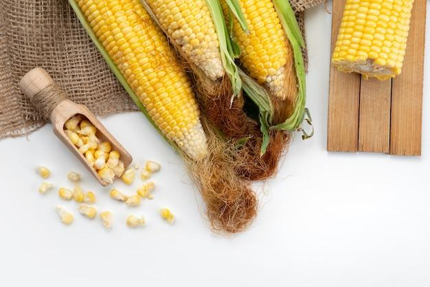 Gelbe körner der draufsicht roh mit grünen blättern auf weißem schreibtisch, lebensmittelmahlzeitfarbmais Kostenlose Fotos