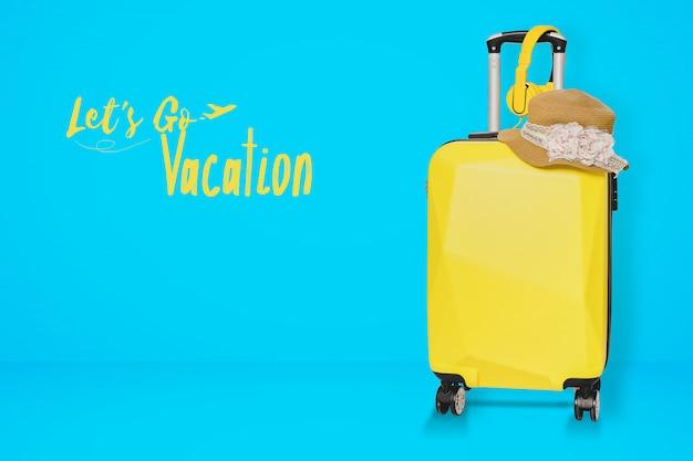 Gelbe koffertasche mit hut und kopfhörer auf blauem hintergrund. Premium Fotos
