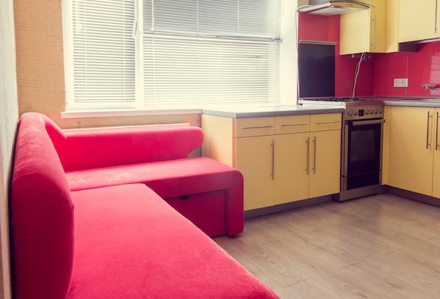 Gelbe küche mit schränken, fenster, laminat und roter weicher couch Premium Fotos