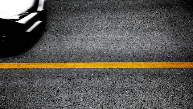 Gelbe lacklinie auf schwarzem asphalt Premium Fotos