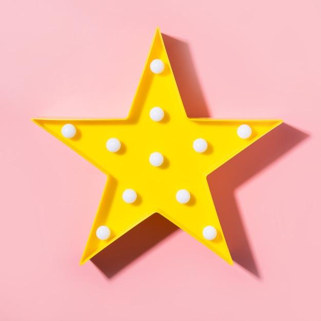 Gelbe lampe als stern mit weißer led beleuchtet auf rosa hintergrund. Premium Fotos