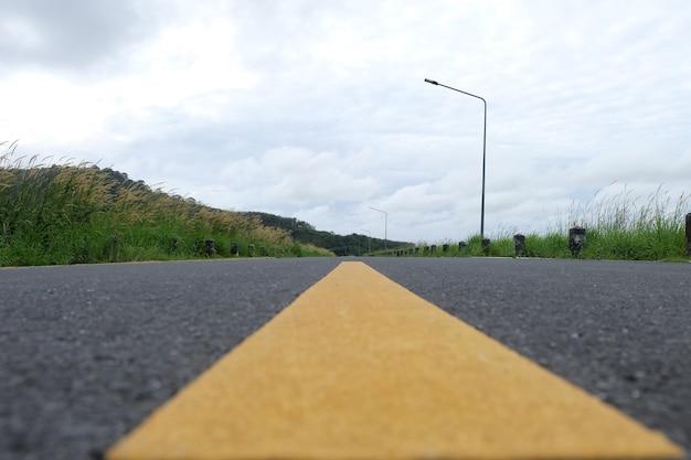 Gelbe linie mit asphaltstraßenbeschaffenheit vor xamountain view close up Premium Fotos