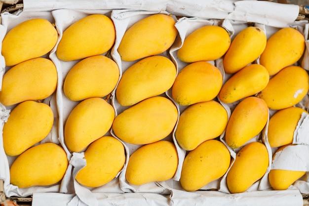 Gelbe mango, die im kasten auf obstmarkt liegt Premium Fotos