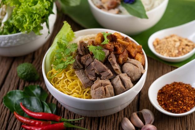 Gelbe nudeln in einer tasse mit knusprigem schweinefleisch, schweinefleischscheiben und fleischbällchen zusammen mit thailändischen nudeln Kostenlose Fotos