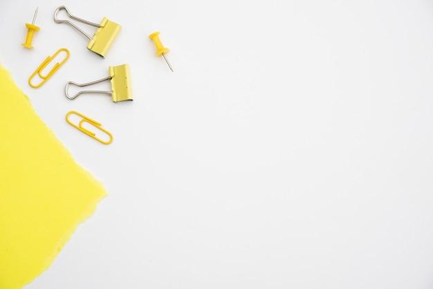 Gelbe papierklammer und druckbolzen auf weißem hintergrund mit kopienraum Kostenlose Fotos