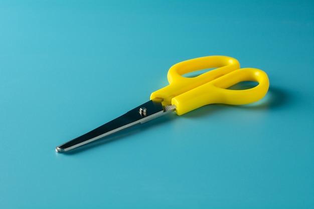 Gelbe plastikscheren auf blauem papier. - hintergrund Premium Fotos