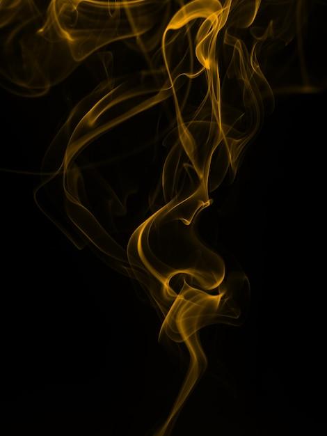 Gelbe rauchzusammenfassung auf schwarzem hintergrund, feuer Premium Fotos
