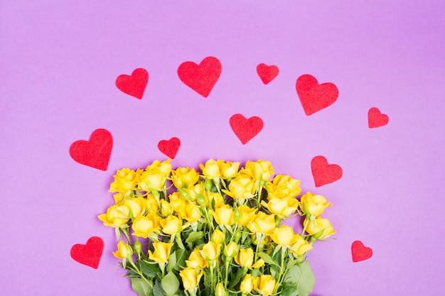 Gelbe rosa rosenblumen mit roten herzen auf lila tischhintergrund Premium Fotos