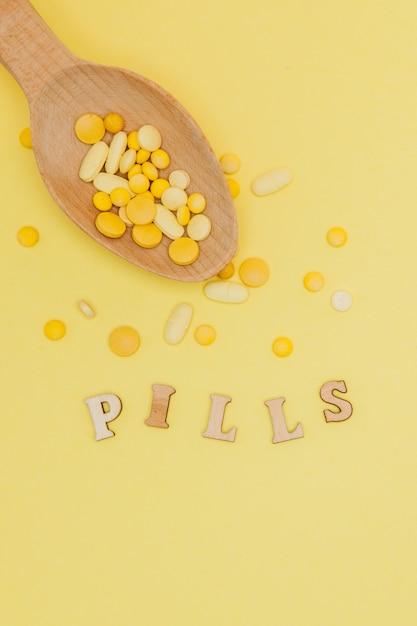 Gelbe runde vitaminpillen im löffel auf gelbem hintergrund Premium Fotos