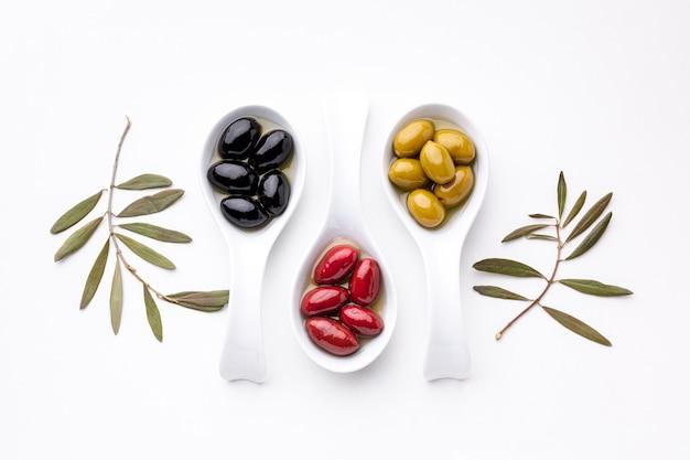 Gelbe schwarze rote oliven in den löffeln mit blättern Kostenlose Fotos