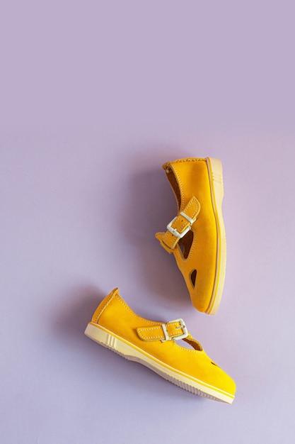 Gelbe sommersandalen der frauen auf lila hintergrund mit kopienraum. vertikales foto. sicht von oben. Premium Fotos