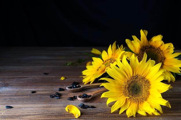 Gelbe sonnenblumen auf hintergrund des alten zauns. Premium Fotos
