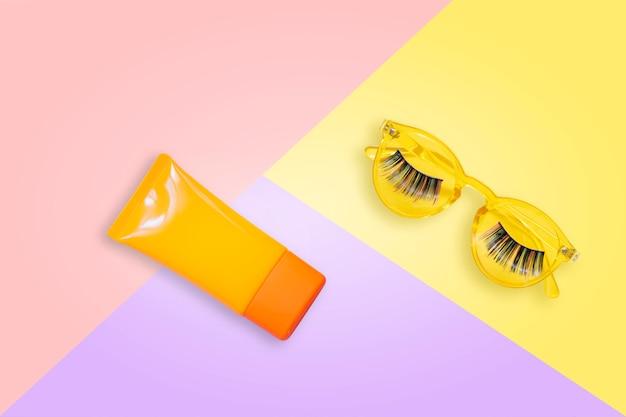 Gelbe sonnenbrille mit den gefälschten wimpern und orange lichtschutz spf creme auf rosa hintergrund. Premium Fotos