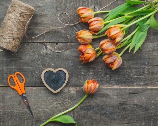 Gelbe tulpen mit rustikalem thread auf einem holztisch. Kostenlose Fotos