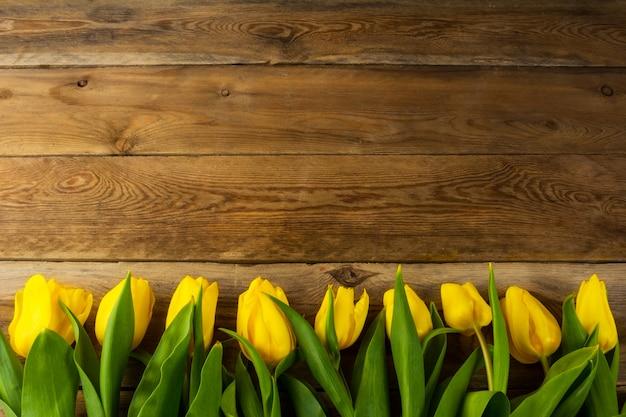 Gelbe tulpen rudern auf hölzernem hintergrund, kopienraum Premium Fotos