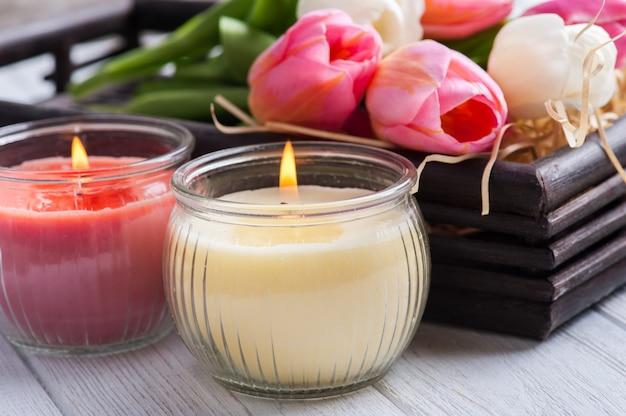 Gelbe und rosa duftkerzen mit tulpen Premium Fotos