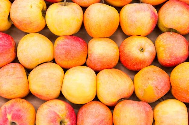 Gelbe und rote äpfel im shop. textur von äpfeln Premium Fotos