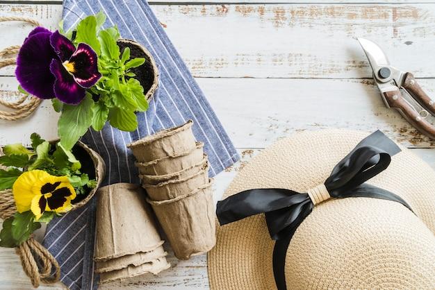 Gelbe und violette stiefmütterchenblüte mit gartenschere; hut; torftöpfe und -serviette auf hölzernem schreibtisch Kostenlose Fotos