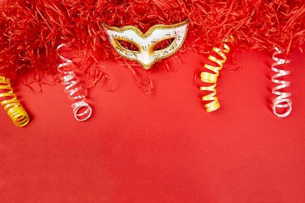 Gelbe und weiße karnevalsmaske auf rot Premium Fotos