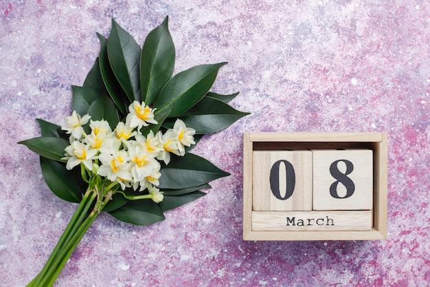 Gelbe weiße narzisse, narzisse, jonquilleblume auf rosa beton. 8. märz frauentag. Premium Fotos