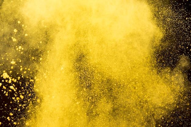 Gelbe wolke des kosmetischen puders auf schwarzem hintergrund Kostenlose Fotos