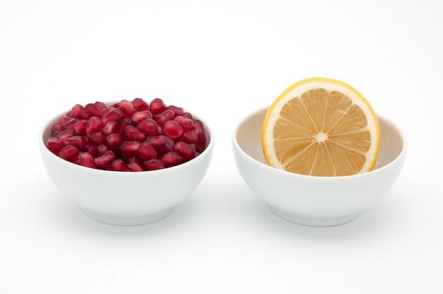 Gelbe zitrone und rote samen des granatapfels in den schalen auf einem weißen hintergrund. Premium Fotos