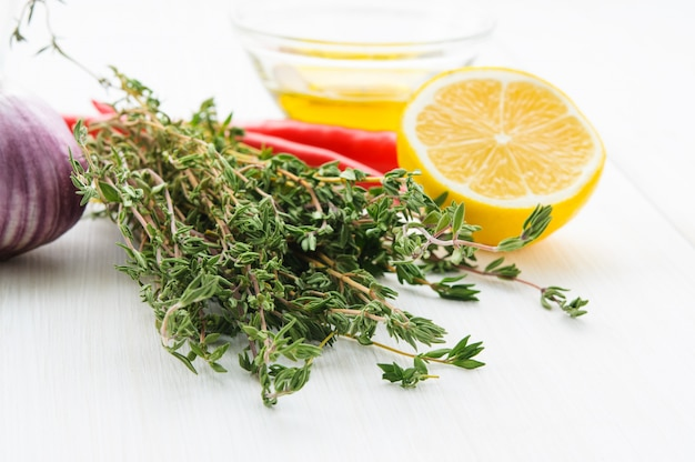 Gelbe zitronenhälfte, grüner thyne branch chili pepper, olivenöl, knoblauch Premium Fotos
