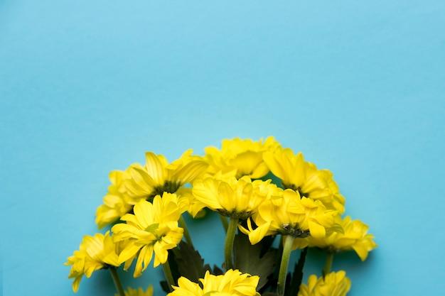 Gelber blumenblumenstrauß auf blauem hintergrund Kostenlose Fotos