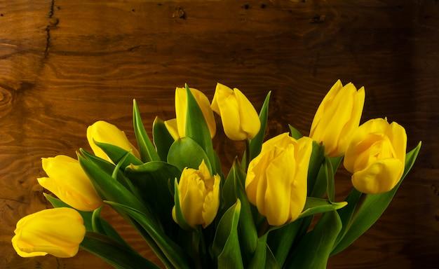 Gelber blumenstrauß des frühlinges auf hölzernem hintergrund Premium Fotos