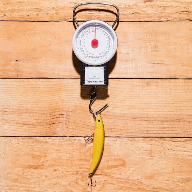 Gelber fischereiköder, der an messender skala über dem hölzernen schreibtisch hängt Kostenlose Fotos