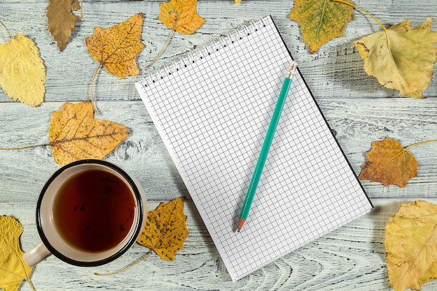 Gelber herbstlaub, eine tasse tee und ein notizbuch auf einem hellen alten hölzernen hintergrund Premium Fotos