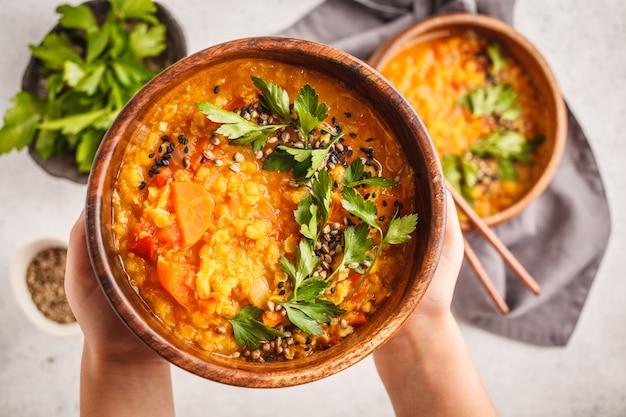 Gelber indischer veganer linsensuppecurry mit petersilie und indischem sesam in einer hölzernen schüssel in den händen. Premium Fotos