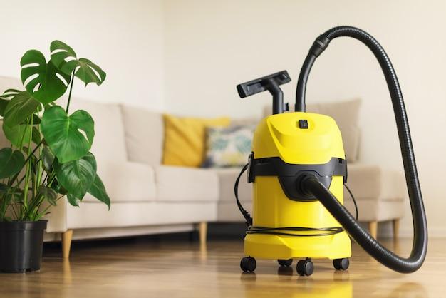 Gelber moderner staubsauger im wohnzimmer. kopieren sie platz. flaches sauberes staubsaugerkonzept. grüne monsterpflanze Premium Fotos