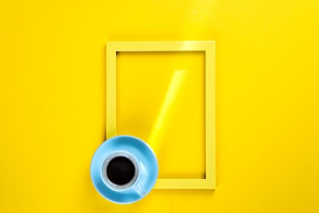Gelber rahmen mit einem sonnenstrahl und einer tasse tee auf ihm, draufsicht über einen gelben hintergrund, platz für text Premium Fotos