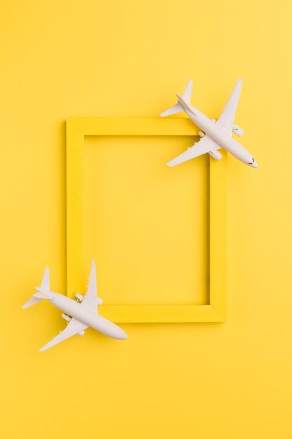 Gelber rahmen mit spielzeugflugzeugen Premium Fotos