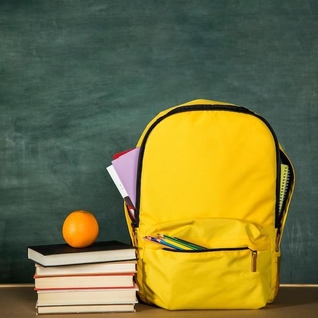 Gelber rucksack, stapel bücher und orange Kostenlose Fotos