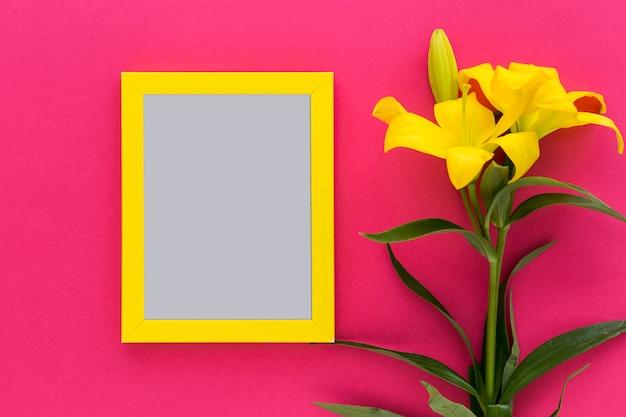 Gelber schwarzer rahmen mit gelber lilienblume und -knospe auf rosa hintergrund Kostenlose Fotos