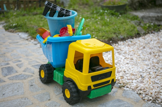 Gelber spielzeuglastwagen im hof Kostenlose Fotos