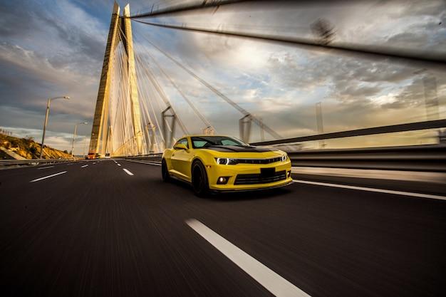 Gelber sportwagen mit schwarzem autotuning auf der brücke. Kostenlose Fotos