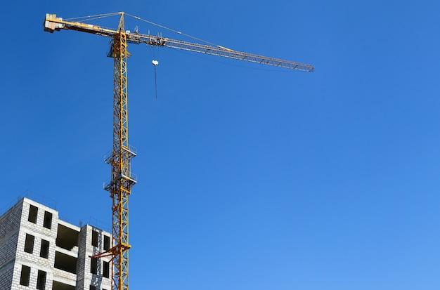 Gelber turmkran beim bauen eines hauses gegen einen blauen himmel Premium Fotos