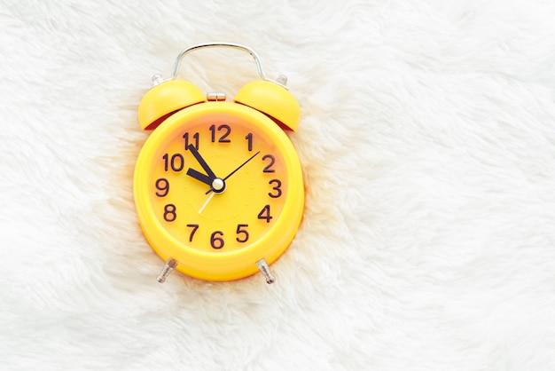Gelber wecker auf weißer wolle. spätes und faules zeitkonzept Premium Fotos