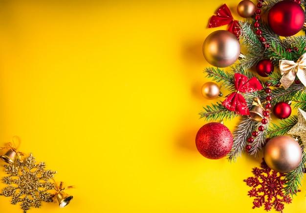 Gelber weihnachtshintergrund verziert mit tannenbaum und spielwaren Premium Fotos