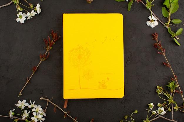 Gelbes bild der draufsicht zusammen mit blumen auf dem dunklen boden Kostenlose Fotos