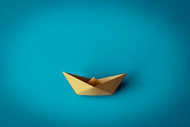 Gelbes papierboot auf blauem hintergrund mit kopienraum, lern- und bildungskonzept Premium Fotos