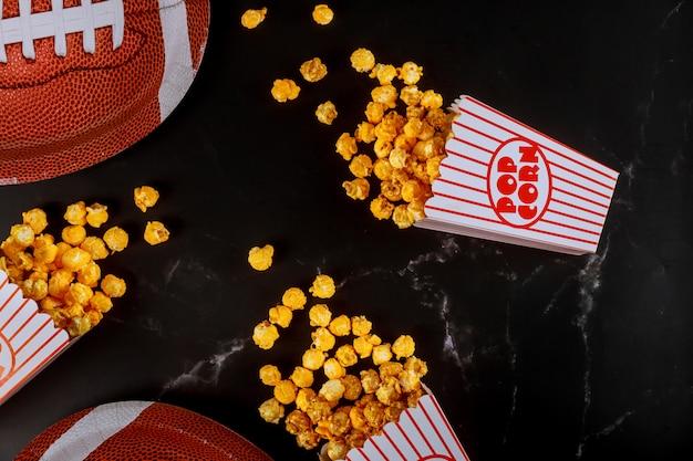 Gelbes popcorn in gestreiften kisten verschüttet auf schwarzem tisch mit american-football-platte Premium Fotos