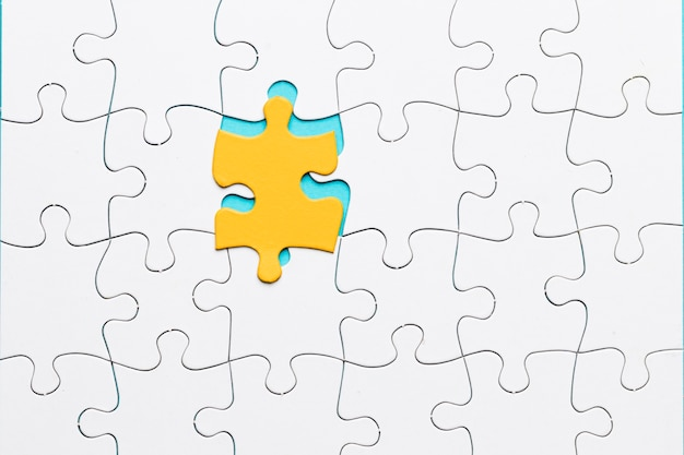 Gelbes puzzleteil mit weißem gitterpuzzlespiel Kostenlose Fotos