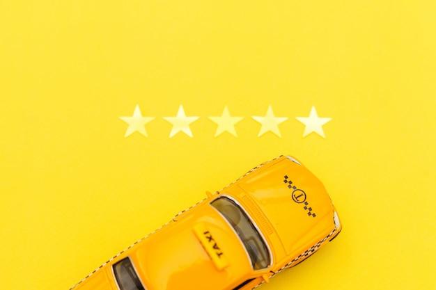 Gelbes spielzeugauto taxi und 5 sterne bewertung isoliert auf gelb. smartphone-anwendung des taxidienstes für die online-suche nach anruf- und buchungskonzepten. taxisymbol. speicherplatz kopieren. Premium Fotos