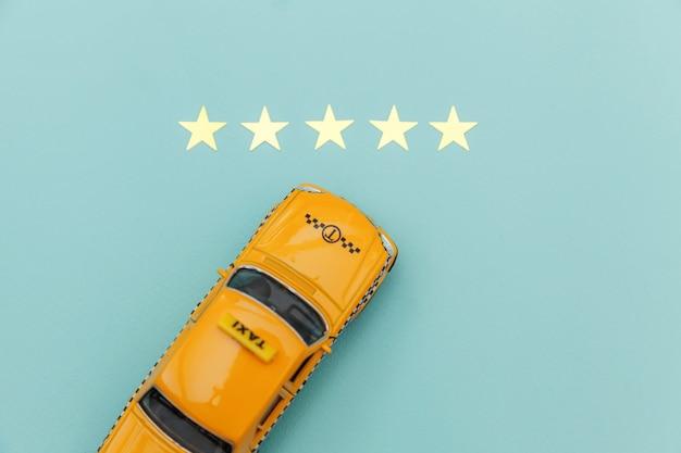 Gelbes spielzeugauto taxi und 5 sterne bewertung lokalisiert auf blauem hintergrund. smartphone-anwendung des taxidienstes für die online-suche nach anruf- und buchungskonzepten. taxisymbol. speicherplatz kopieren. Premium Fotos