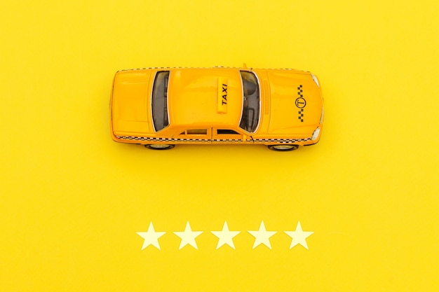 Gelbes spielzeugauto taxi und 5 sterne bewertung lokalisiert auf gelbem hintergrund. Premium Fotos